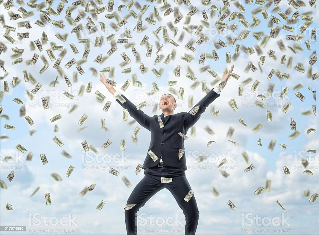 Happy businessman in celebrating pose with loads of money in stock photo