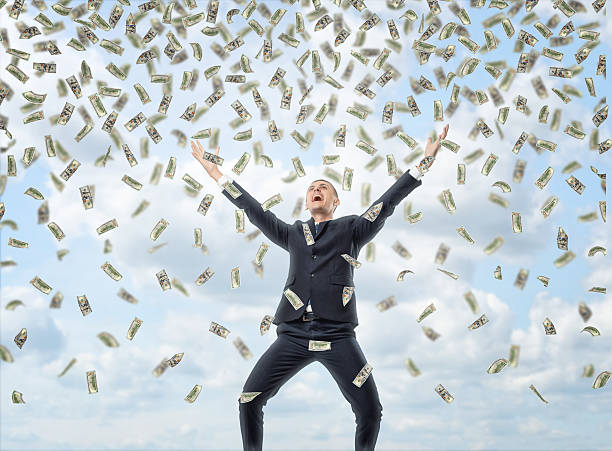 Happy businessman in celebrating pose with loads of money in - foto de acervo