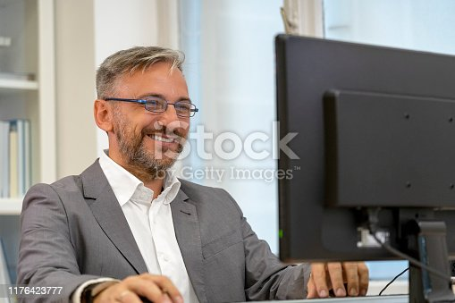 Successful Mature Businessman Sitting at Office Desk. Smiling Elegant Man Looking at Computer Monitor in His Office.
