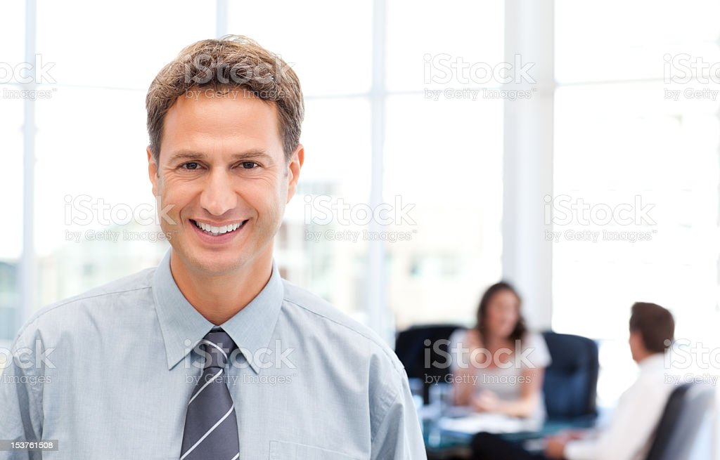 Happy businessman in the foreground while his team is working Happy businessman in the foreground while his team is working at a table Adult Stock Photo