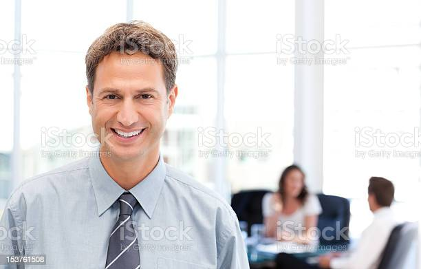 Happy Businessman In The Foreground While His Team Is Working Stock Photo - Download Image Now