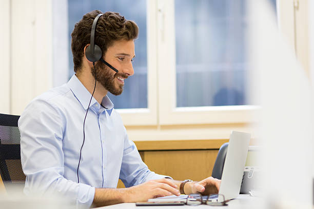 Happy Businessman in the office on the phone, headset, Skype stock photo
