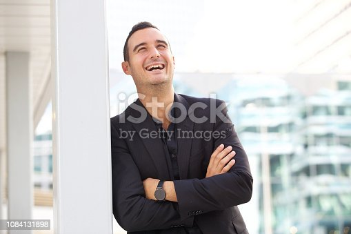 istock happy businessman leaning against post outside in the city 1084131898