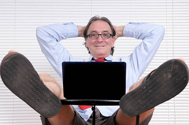 happy businessman looking pc - old man feet stock photos and pictures