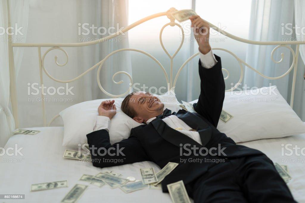 Heureux homme d'affaires, allongée sur lit, tandis que de regard dollars et souriant. apprécier et couché sur l'argent - Photo