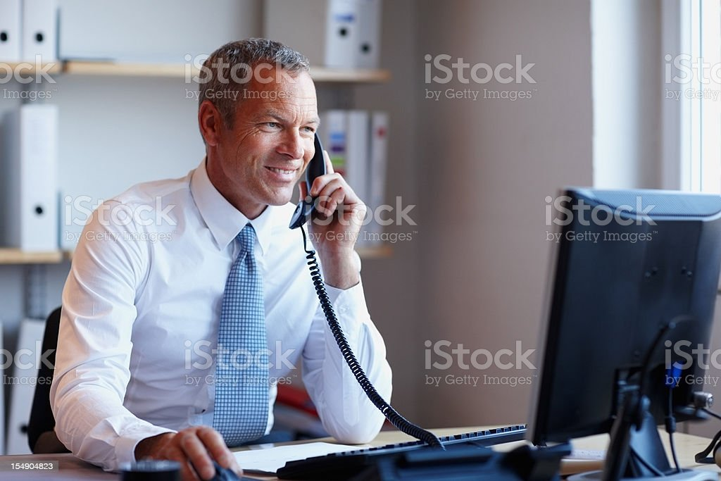 Happy businessman on phone while using computer in the office stock photo