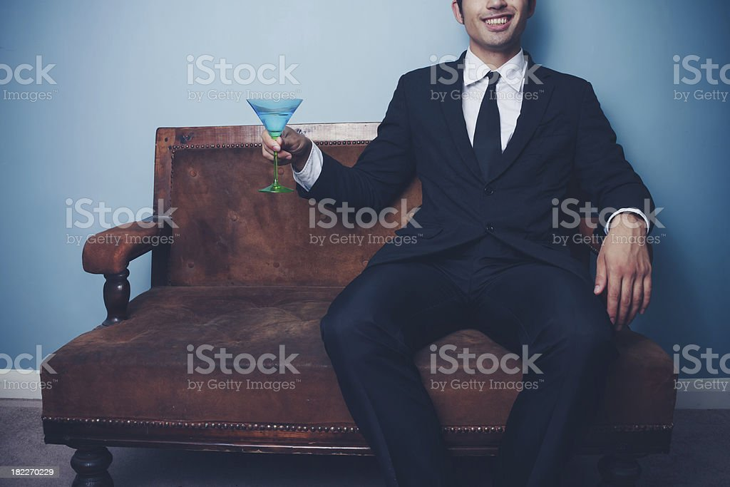 Happy businessman on sofa drinking cocktail royalty-free stock photo