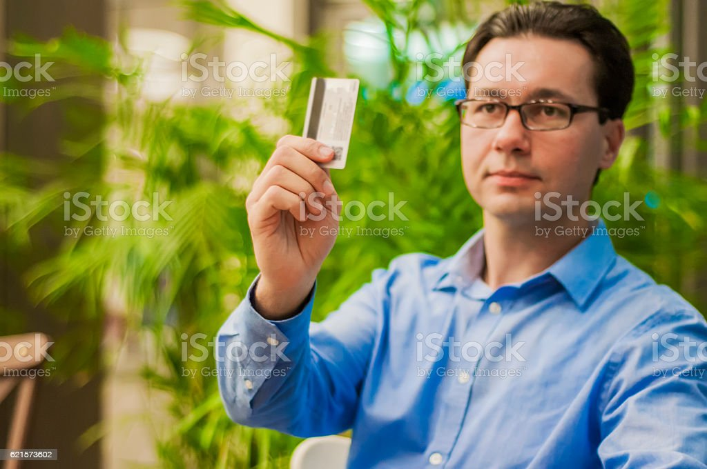 Happy businessman passing his credit card to waiter in cafe. photo libre de droits