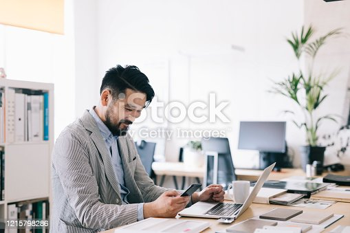Positive Asian small business owner checking his smartphone at work.