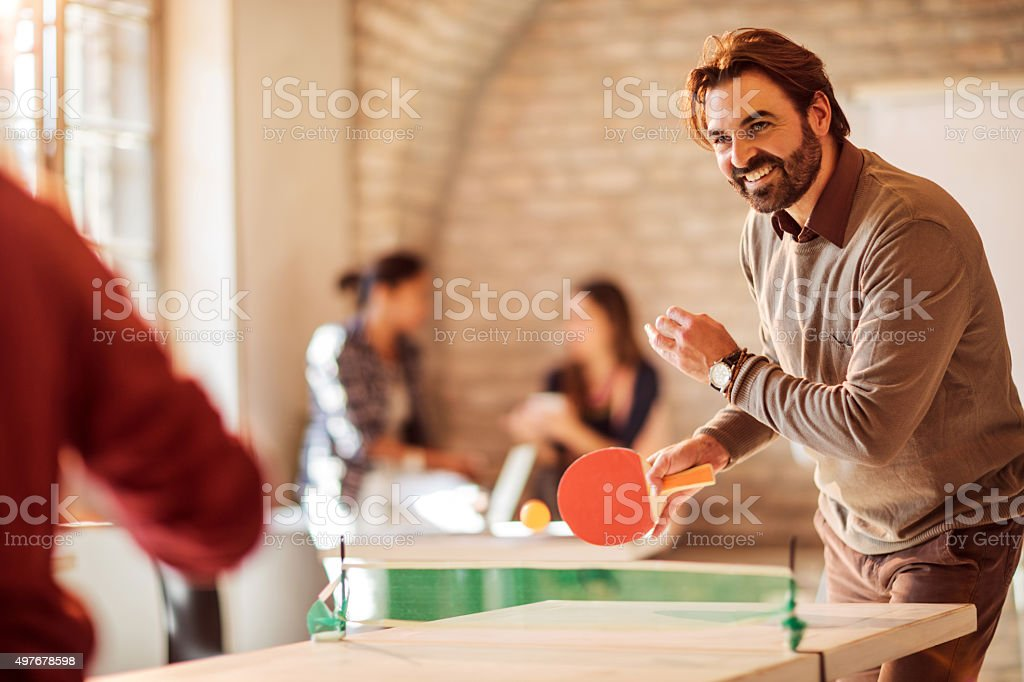 Happy businessman playing table tennis with his colleague at office. stock photo