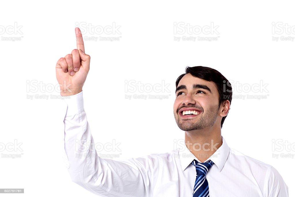 Happy businessman pointing upwards stock photo