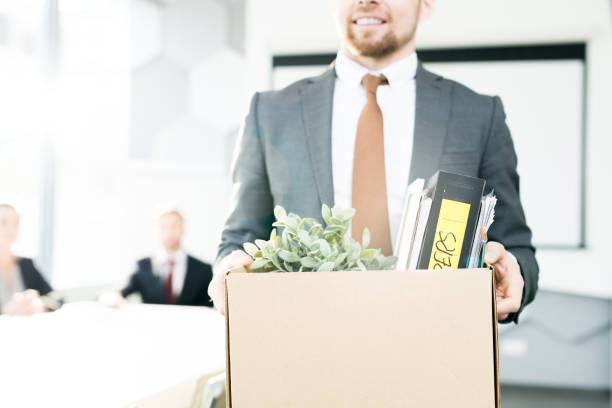 Happy Businessman Quitting Job Mid section portrait of smiling businessman holding box of personal belongings leaving office after quitting job, copy space quitting a job stock pictures, royalty-free photos & images
