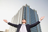 Happy businessman raising hands