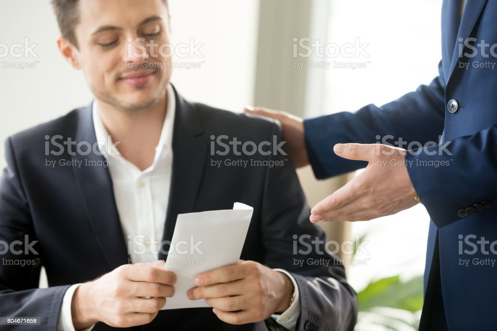 Happy businessman receiving white envelope with bribe, bribery corruption concept stock photo