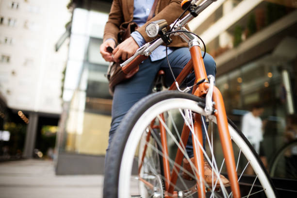 Happy businessman riding bicycle to work in morning stock photo