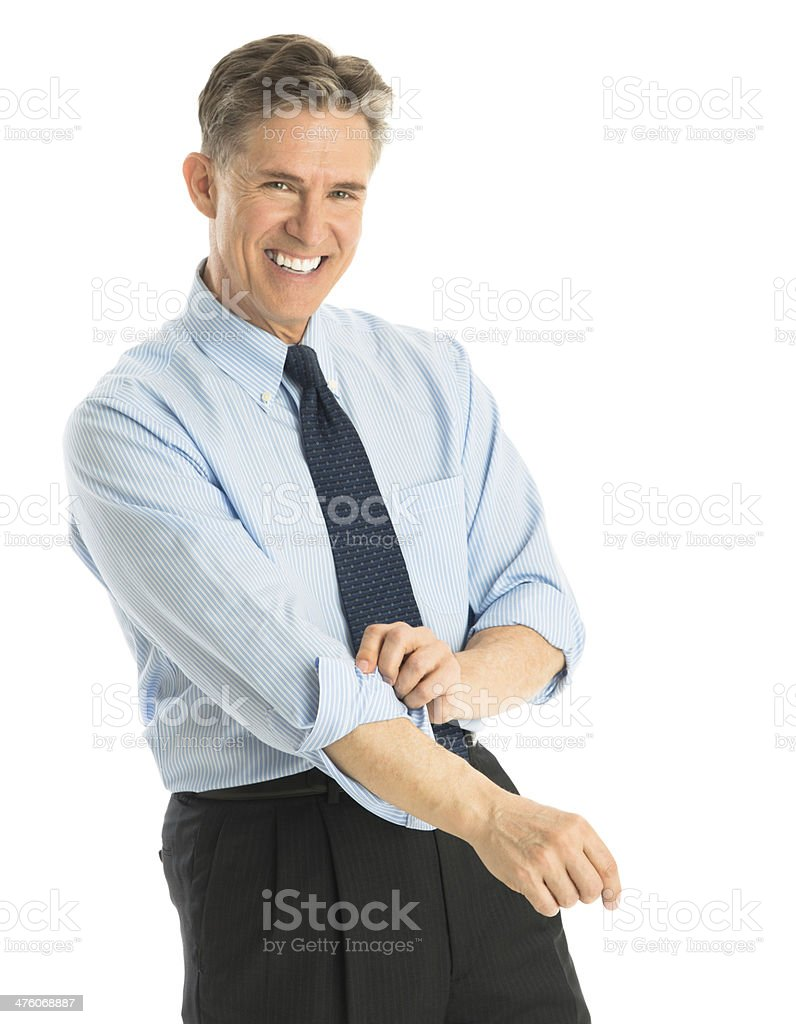 Happy Businessman Rolling Up His Sleeves stock photo