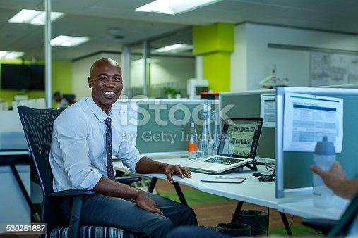 530281723istockphoto Happy businessman sitting at desk 530281687