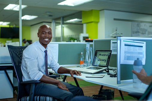 530281733 istock photo Happy businessman sitting at desk 530281687