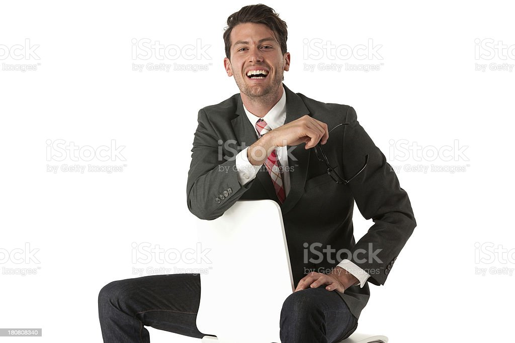 Happy businessman sitting backwards on a chair royalty-free stock photo