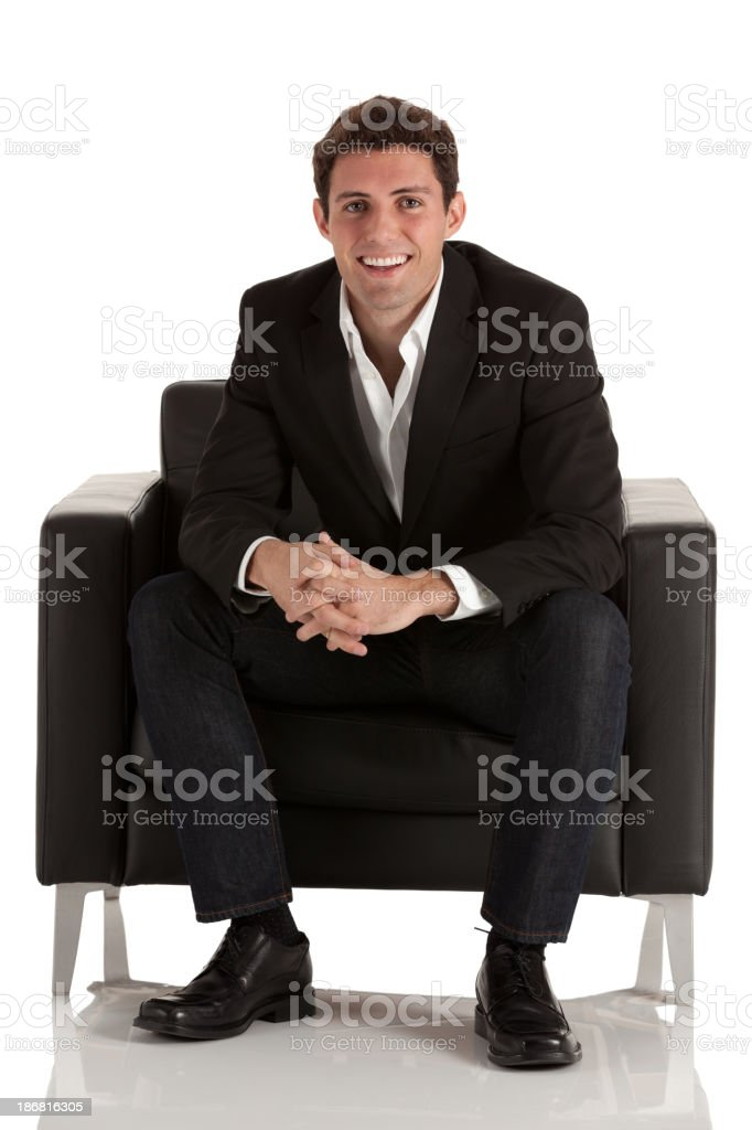 Happy businessman sitting in an armchair stock photo