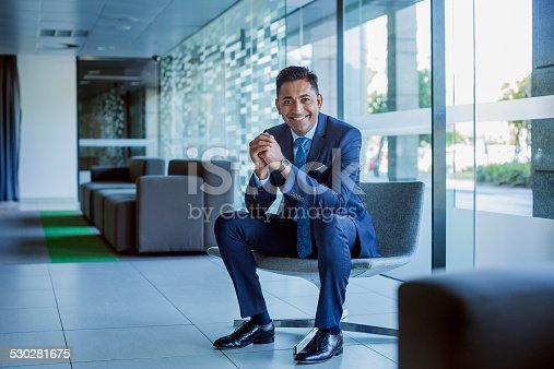 Full length portrait of happy businessman sitting with hands clasped in office lobby