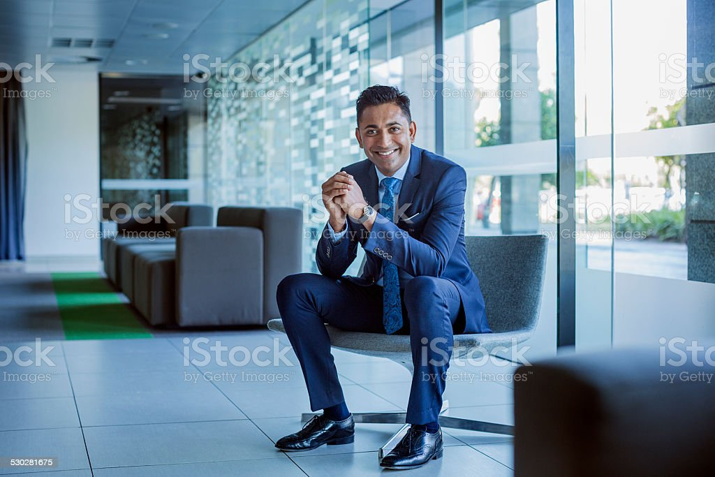 Happy businessman sitting in office lobby stock photo