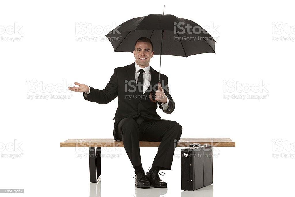 Happy businessman sitting on a bench under an umbrella stock photo