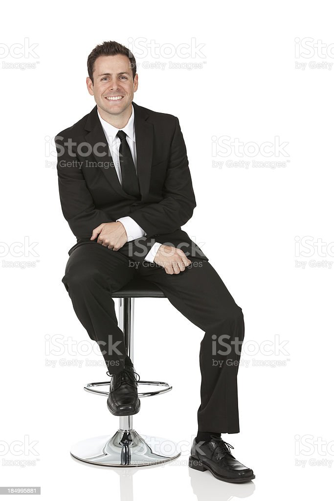 Happy businessman sitting on a chair stock photo