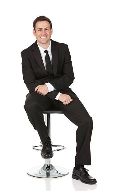 ハッピーな椅子に座っているビジネスマン ストックフォト