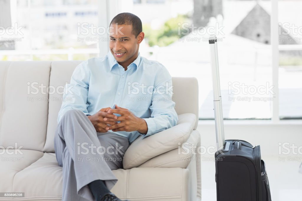 Happy businessman sitting on sofa waiting to depart on business trip stock photo