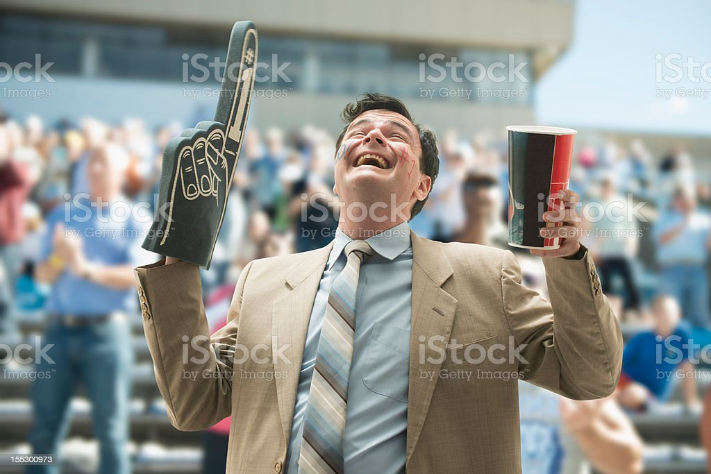 Happy businessman sports fan with foam hand and drink stock photo