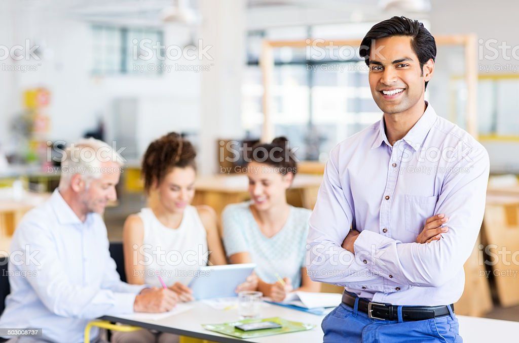 Happy Businessman Standing Arms Crossed At Office stock photo