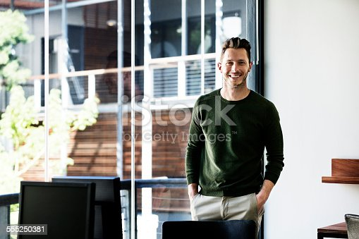 Portrait of happy businessman standing with hands in pockets by window in office