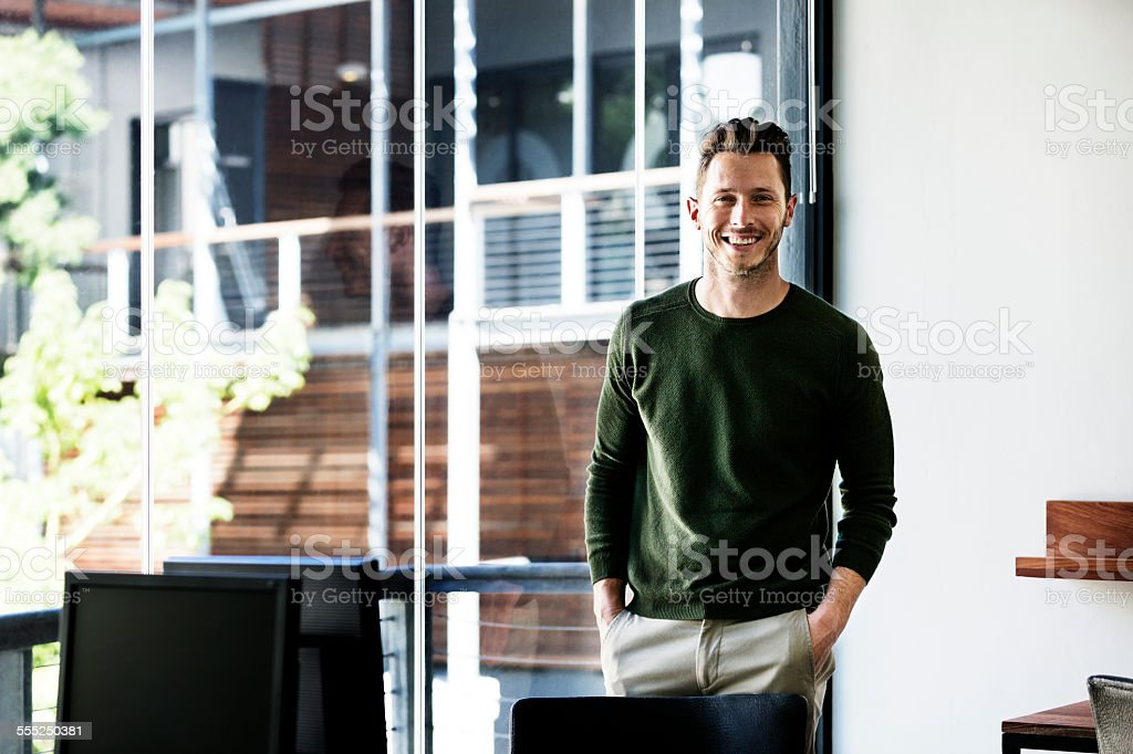Happy businessman standing by window in office stock photo