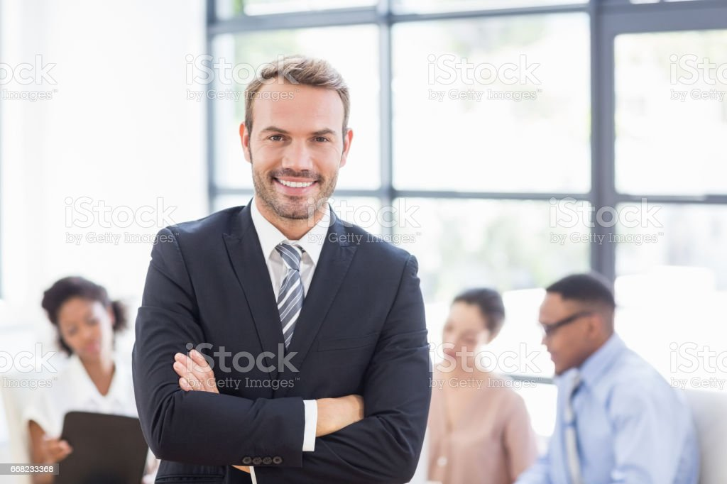 Happy businessman standing with arms crossed stock photo