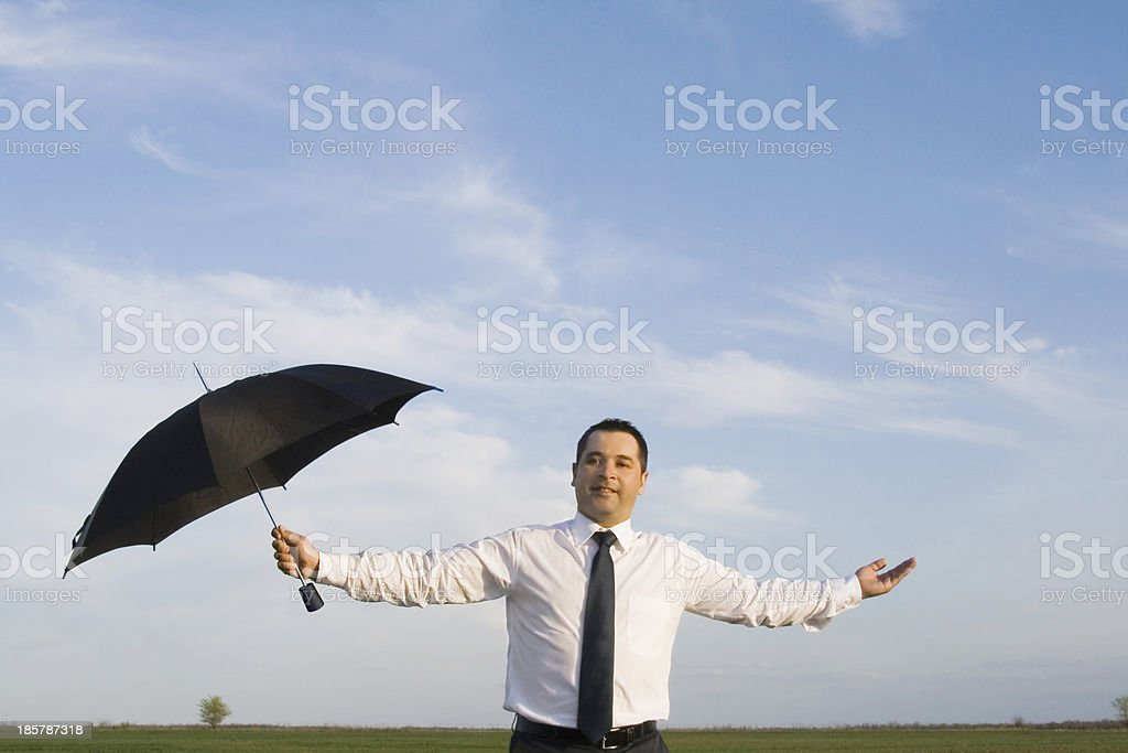 Happy businessman standing with umbrella in the meadow royalty-free stock photo