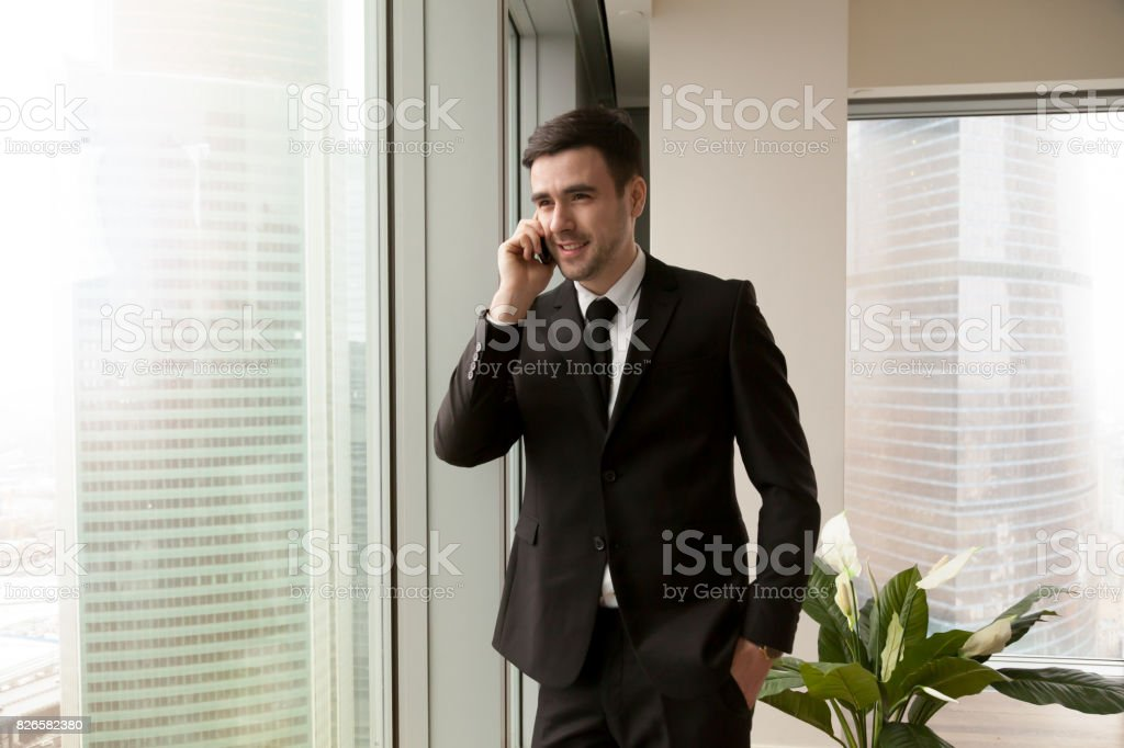 Young happy businessman talking on cell standing near big office...
