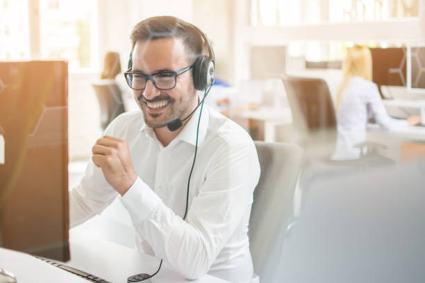 Happy businessman talking on headset in office. Through glass view stock photo
