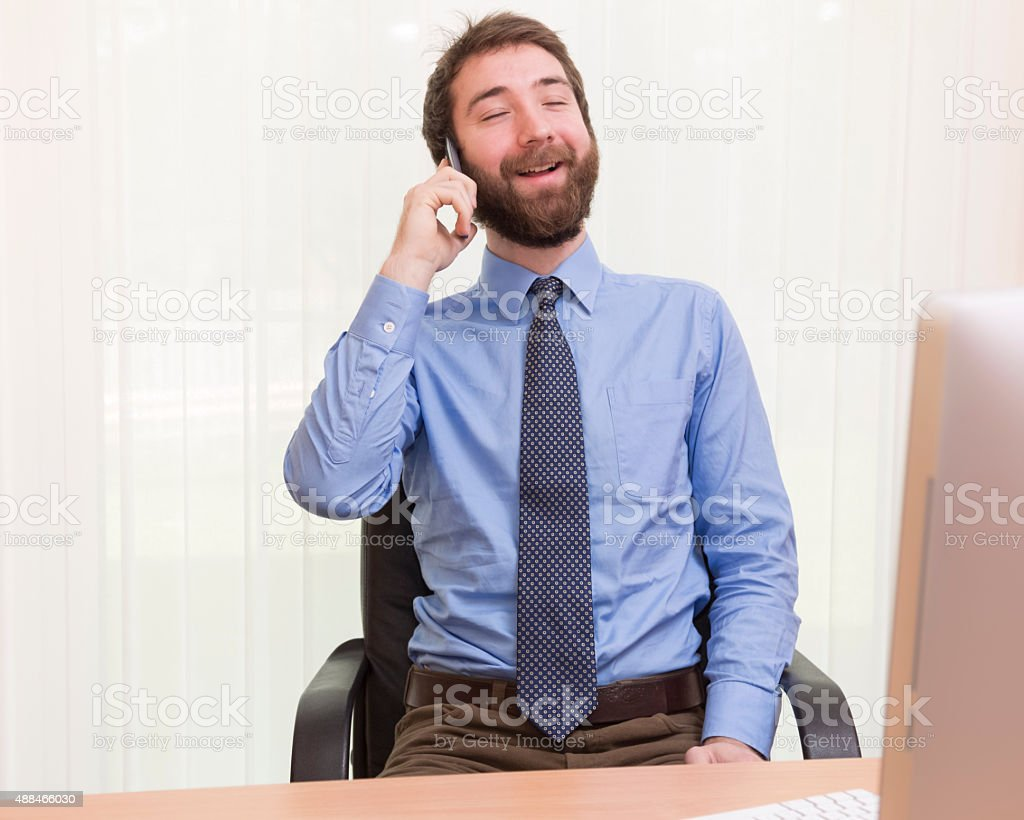 Happy businessman talking on the phone in the office. stock photo