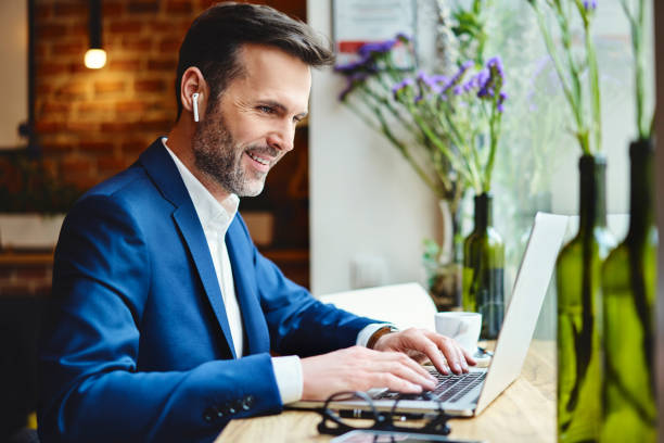 Glücklicher Geschäftsmann im Gespräch mit drahtlosen Kopfhörern während der Arbeit am Laptop im Café – Foto