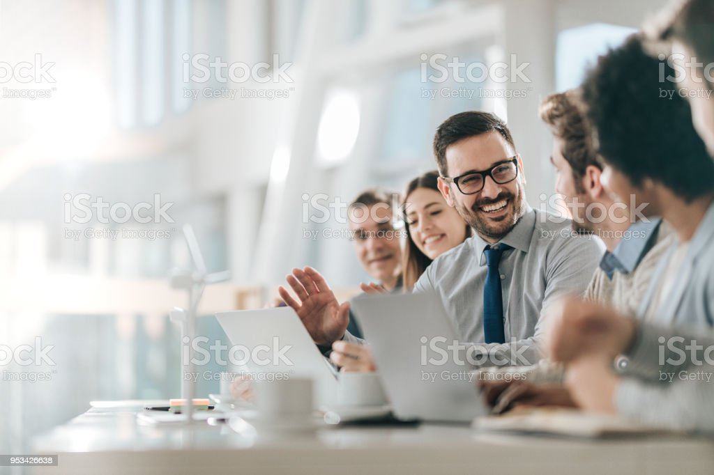 Happy businessman talking to his colleagues on a meeting in the office, stock photo