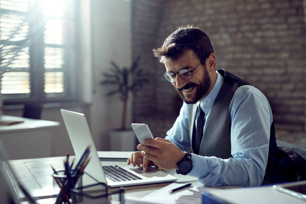 Happy businessman texting on mobile phone while working in the office. stock photo