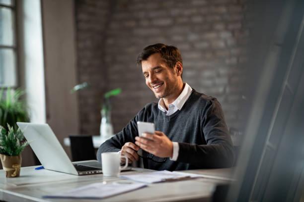 glücklicher geschäftsmann texting auf handy während der arbeit auf laptop im büro. - einzelner mann über 30 stock-fotos und bilder