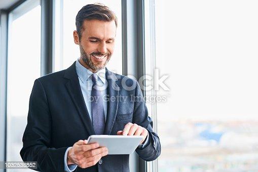 istock Happy businessman using digital tablet standing in office 1032538852