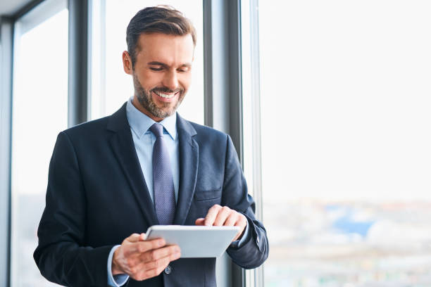 Happy businessman using digital tablet standing in office stock photo