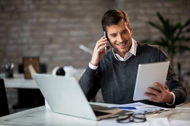 happy zakenman met behulp van digitale tablet tijdens het praten over mobiele telefoon in het kantoor. - mid volwassen mannen stockfoto's en -beelden