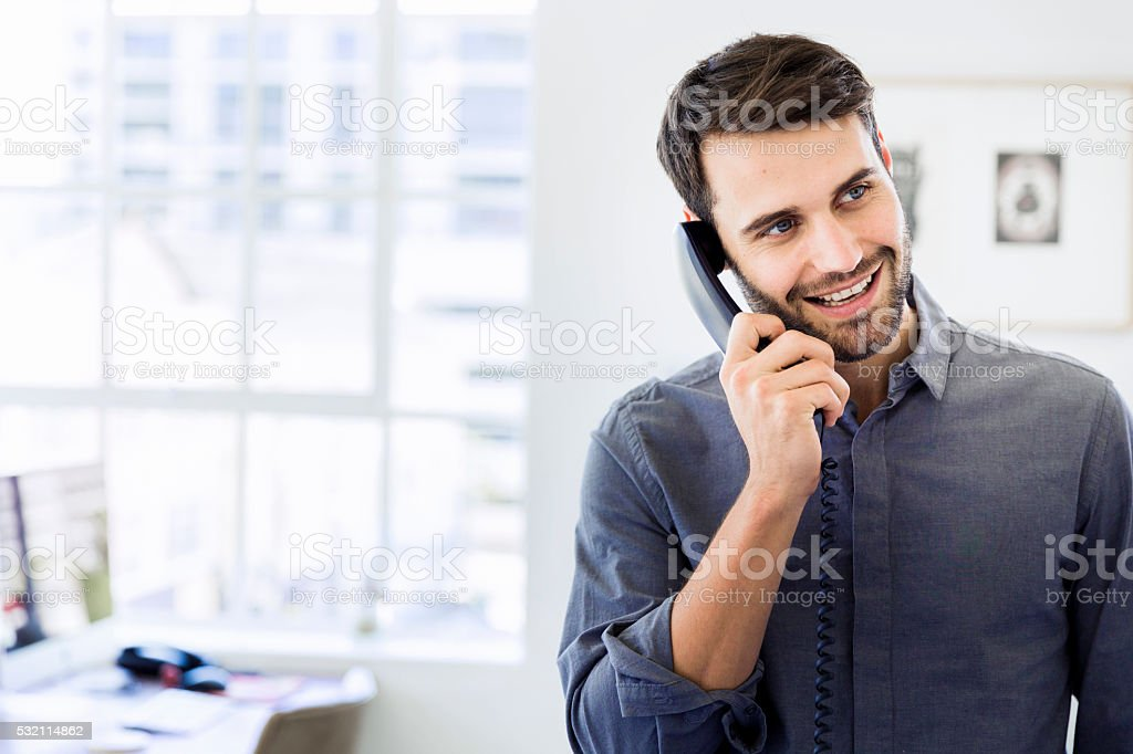 Happy businessman using landline phone in office stock photo