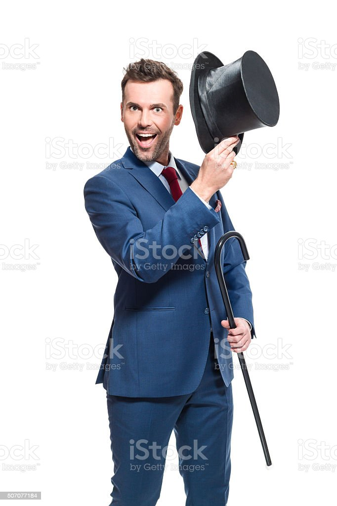 Happy businessman wearing suit, holding cylinder hat and walkign cane Portrait of elegant businessman wearing suit and cylinder hat, holding walking cane, laughing at the camera. Studio shot, one person, isolated on white. Adult Stock Photo