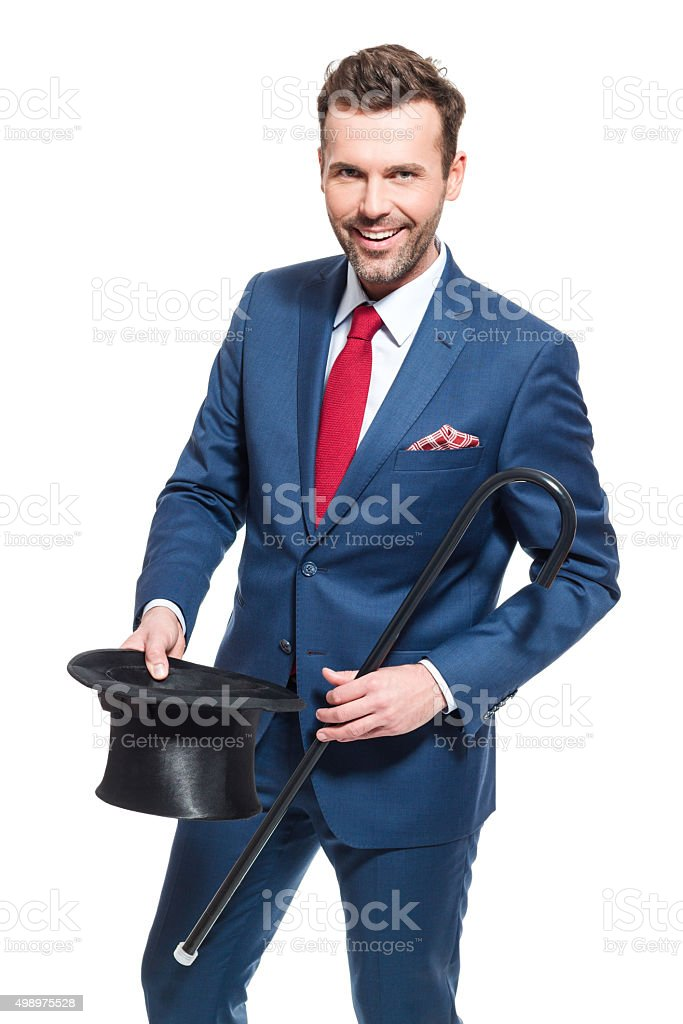 Happy businessman wearing suit, holding cylinder hat and walking cane Portrait of elegant businessman wearing suit, holding cylinder hat and walking cane, smiling at the camera. Studio shot, one person, isolated on white. 2015 Stock Photo