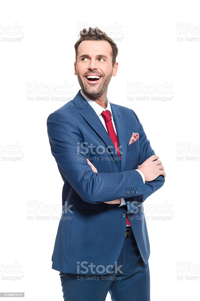 Happy businessman wearing suit, studio portrait Elegant businessman wearing suit, red tie and pocket square, standing against white background. Studio shot, isolated on white.  Adult Stock Photo